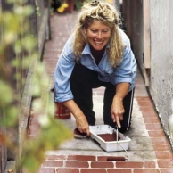 woman painting brick structure on outdoor walkway
